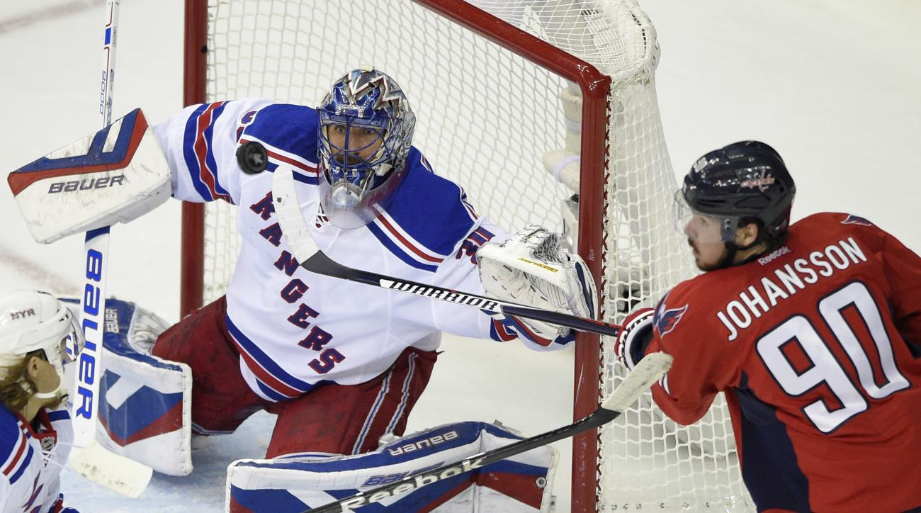 New York Rangers goalie Henrik Lundqvist (30), from Sweden, watches the puck as Washington Capitals left wing Marcus Johansson (90), from Sweden, tries to hit it during the second period of Game 6 in the second round of the NHL Stanley Cup hockey playoffs