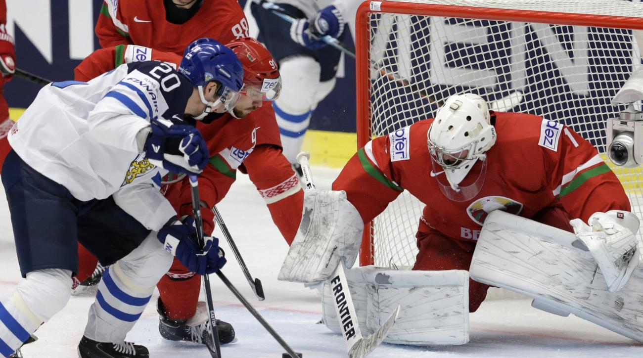 Belarus' Artur Gavrus, center, battles for the puck with Finland's Janne Pesonen, left, in front of Belarus' Vitali Koval during the Hockey World Championships Group B match in Ostrava, Czech Republic, Monday, May 11, 2015. (AP Photo/Sergei Grits)