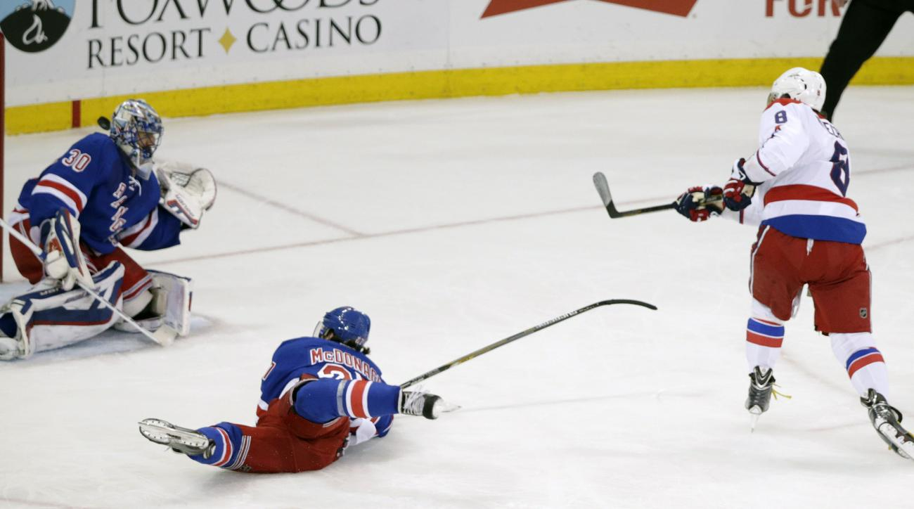 The puck, shot by Washington Capitals left wing Alex Ovechkin (8) slips past New York Rangers goalie Henrik Lundqvist (30) for a goal during the first period of  of Game 7 of the Eastern Conference semifinals during the NHL hockey Stanley Cup playoffs Wed