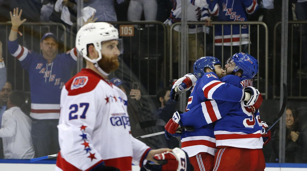 New York Rangers left wing Tanner Glass (15) and defenseman Keith Yandle (93) celebrate after center Derek Stepan (21) scored the game winning goal against the Washington Capitals in overtime of Game 7 of the Eastern Conference semifinals during the NHL h