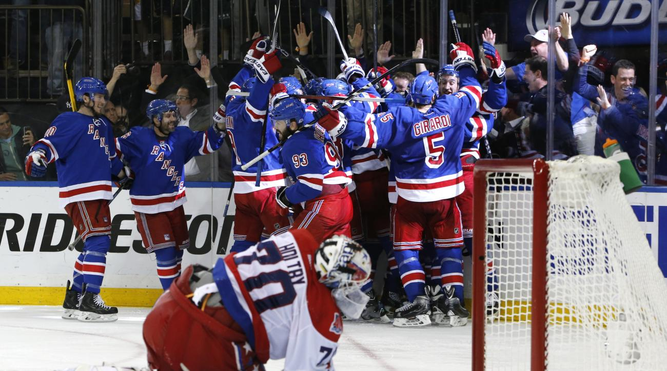 FILE - In this May 13, 2015, file photo, the New York Rangers celebrate the game winning goal by center Derek Stepan (21) against the Washington Capitals as Capitals goalie Braden Holtby looks at the puck in the net in overtime of Game 7 of the Eastern Co
