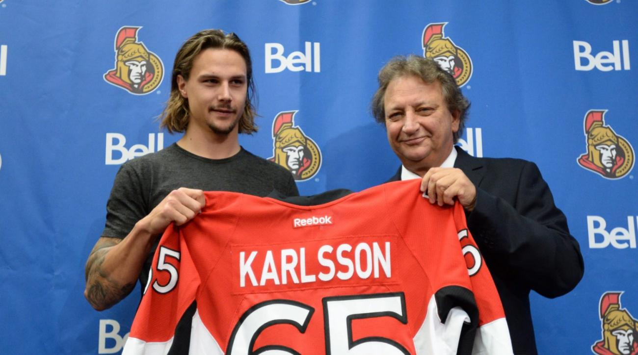 Erik Karlsson, left, and Eugene Melnyk, owner of the Ottawa Senators Hockey Club, hold Karlsson's jersey at a news conference Thursday, Oct.2, 2014 in Ottawa. Karlsson was named captain of the Senators.  (AP Photo/The Canadian Press, Sean Kilpatrick)