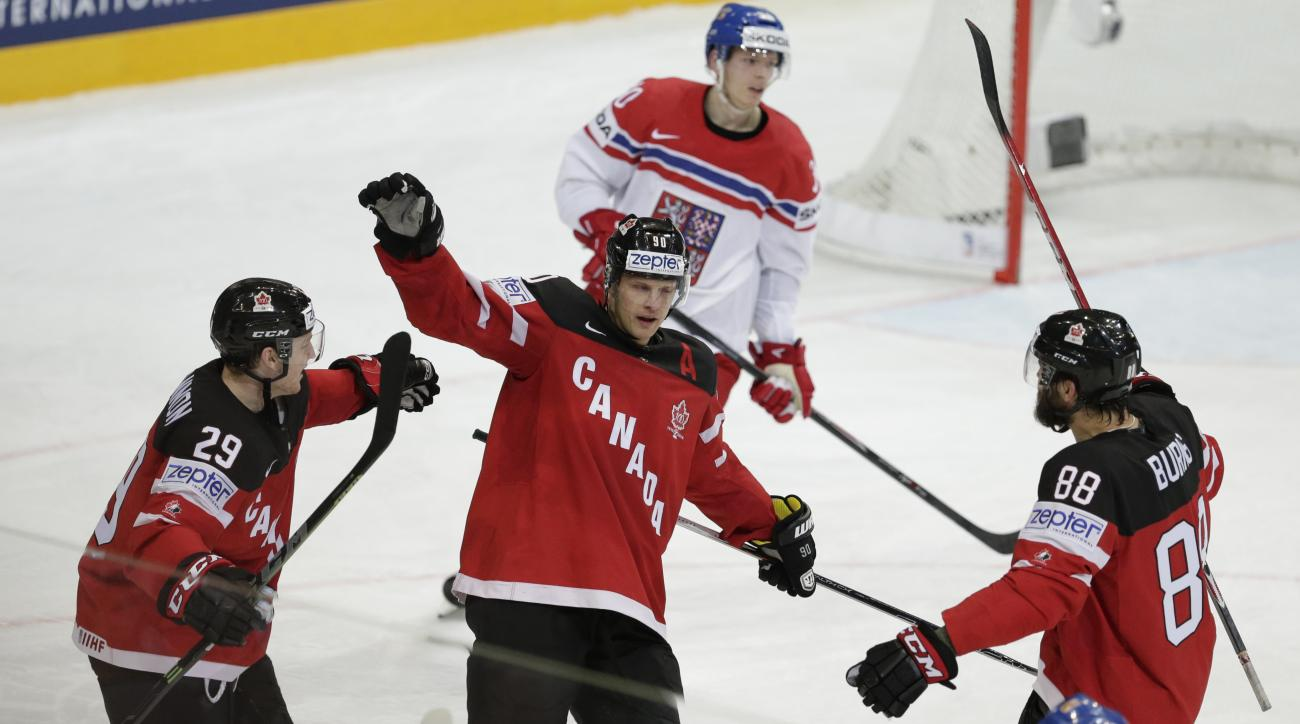 Canada's Jason Spezza, center, celebrates his goal against Czech Republic with teammates Nathan Mackinnon, left, and Brent Burns during the Hockey World Championships semifinal match in Prague, Czech Republic, Saturday, May 16, 2015. (AP Photo/Sergei Grit