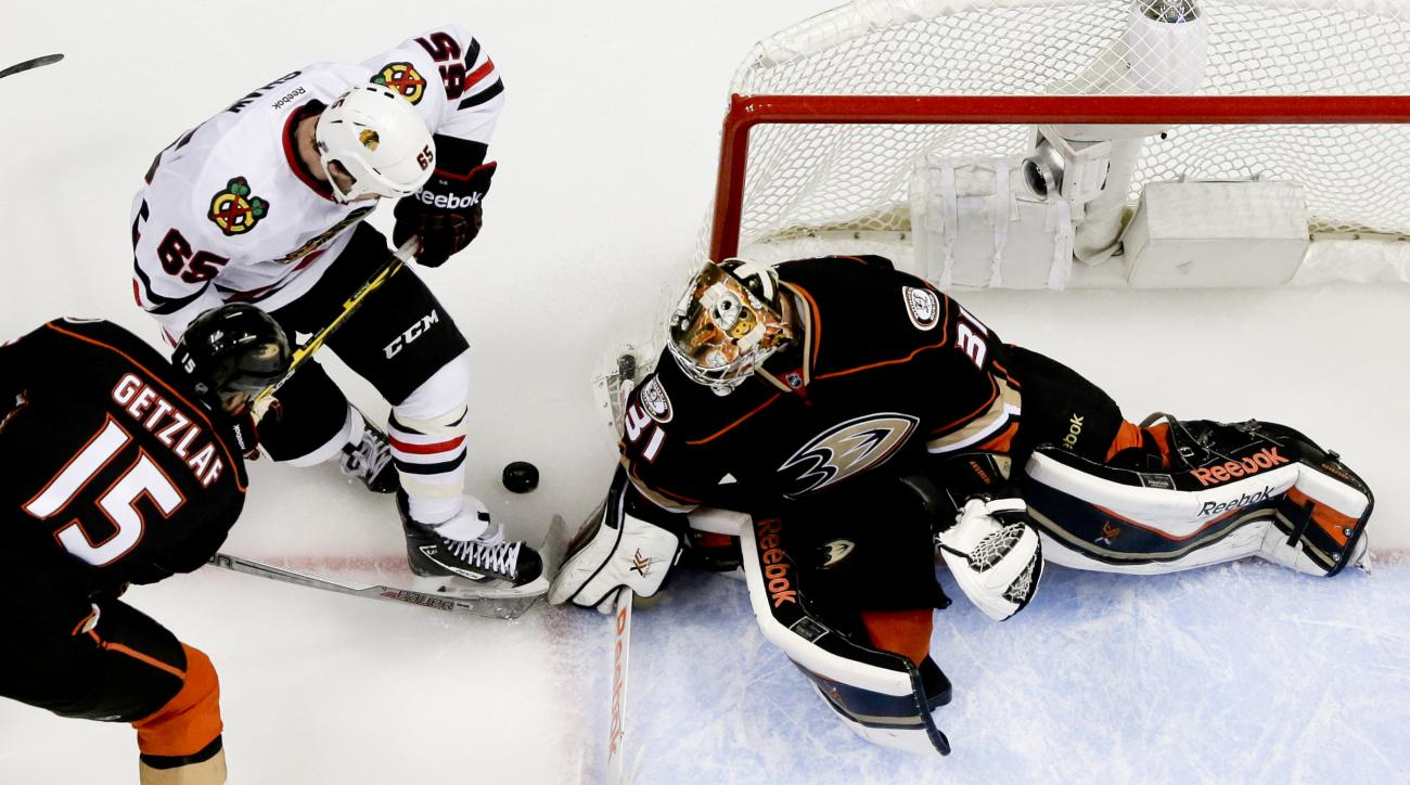 Anaheim Ducks goalie Frederik Andersen, right, blocks a shot by Chicago Blackhawks center Andrew Shaw, as Ryan Getzlaf looks on during the first period of Game 1 of the Western Conference final during the NHL hockey Stanley Cup playoffs in Anaheim, Calif.