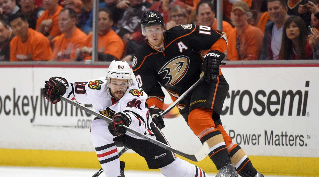 Chicago Blackhawks center Antoine Vermette, left, passes the puck under pressure from Anaheim Ducks right wing Corey Perry during the second period in Game 1 of a Western Conference finals hockey series, Sunday, May 17, 2015, in Anaheim, Calif. (AP Photo/