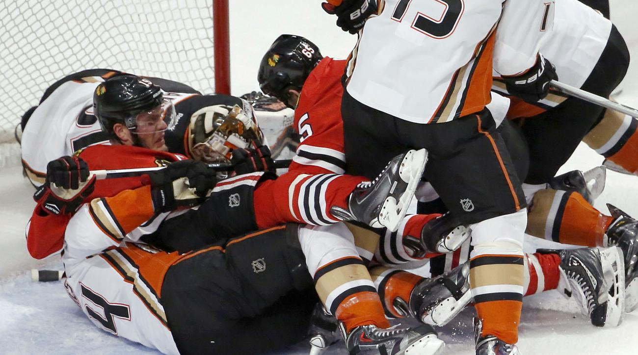 Chicago Blackhawks and Anaheim Ducks players pile up in front of the goal during the first period in Game 3 of the Western Conference finals in the NHL hockey Stanley Cup playoffs, Thursday, May 21, 2015, in Chicago. (AP Photo/Charles Rex Arbogast)