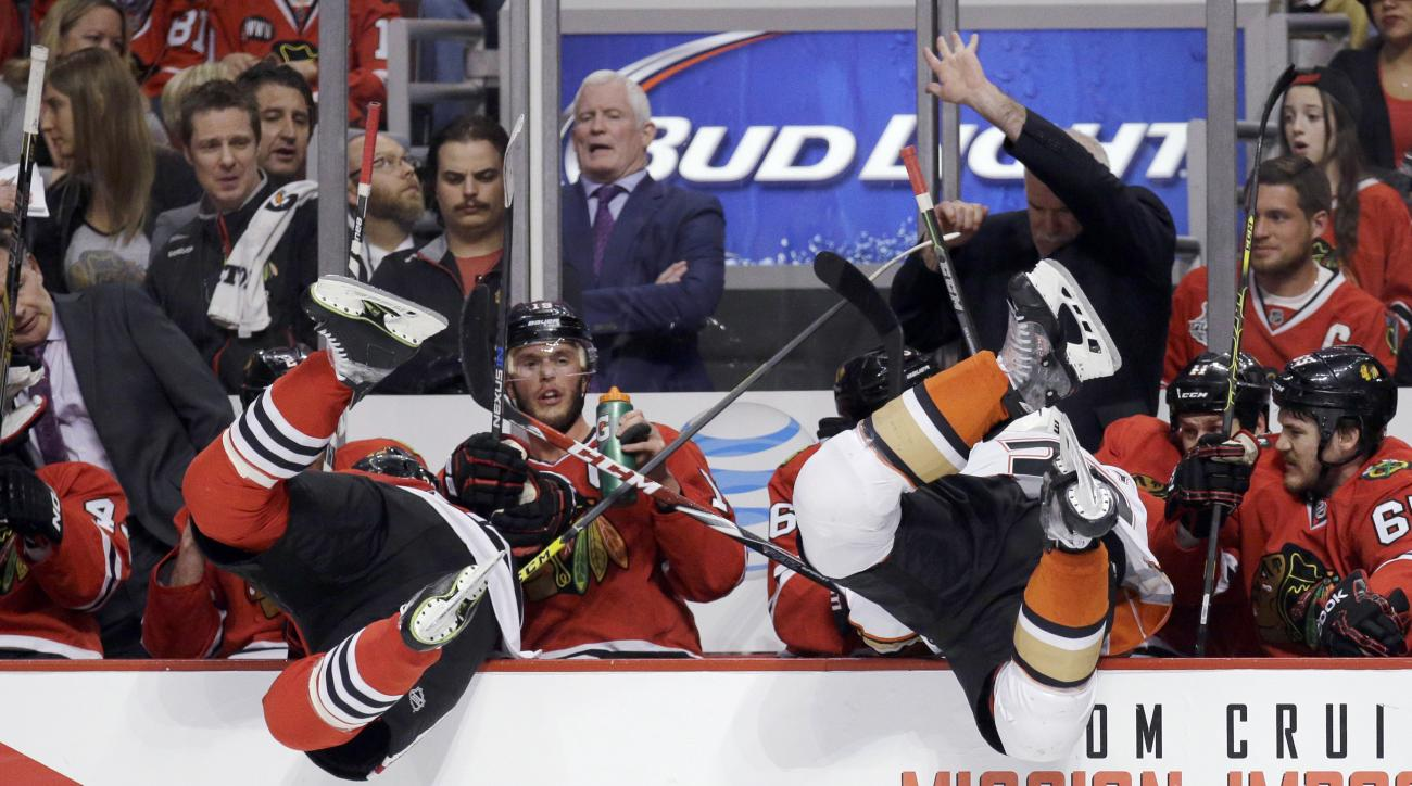 Chicago Blackhawks defenseman Kyle Cumiskey, left, and Anaheim Ducks left wing Matt Beleskey, right, go over the board into the Chicago bench during the second period in Game 4 of the Western Conference finals of the NHL hockey Stanley Cup playoffs, Satur