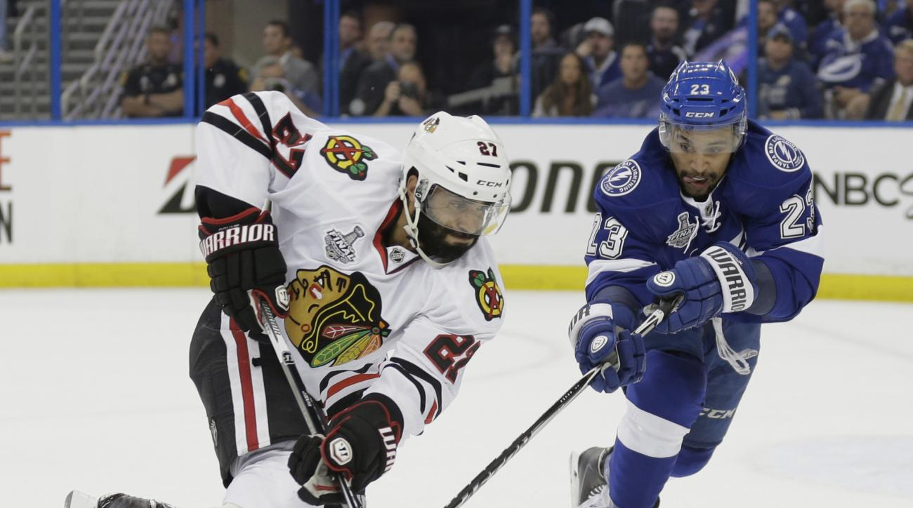 Tampa Bay Lightning right wing J.T. Brown (23) right, battles Chicago Blackhawks defenseman Johnny Oduya (27) for the puck, during the first period in Game 1 of the NHL hockey Stanley Cup Final in Tampa, Fla., Wednesday, June 3, 2015.  (AP Photo/Chris O'M
