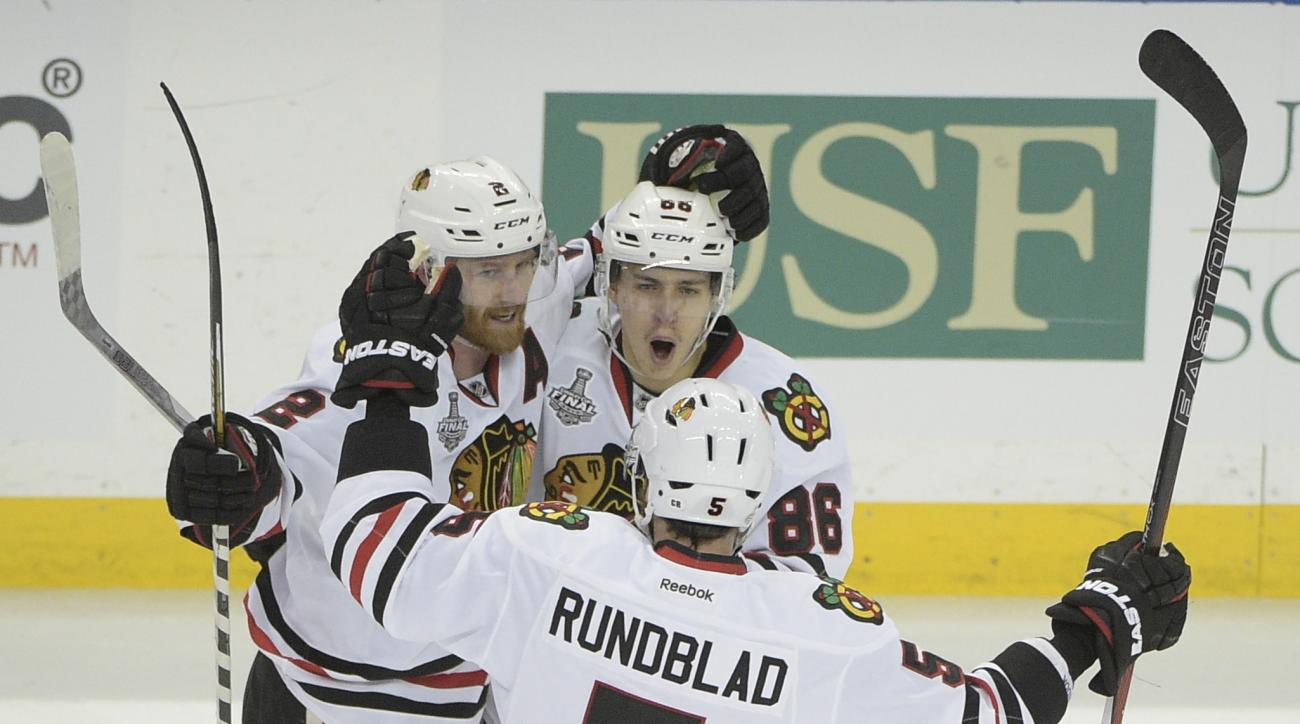 Chicago Blackhawks left wing Teuvo Teravainen (86) of Finland, top right, celebrates his goal with Duncan Keith (2) of Canada, left, and David Rundblad (5) of Sweden, during the third period in Game 1 of the NHL hockey Stanley Cup Final against the Tampa