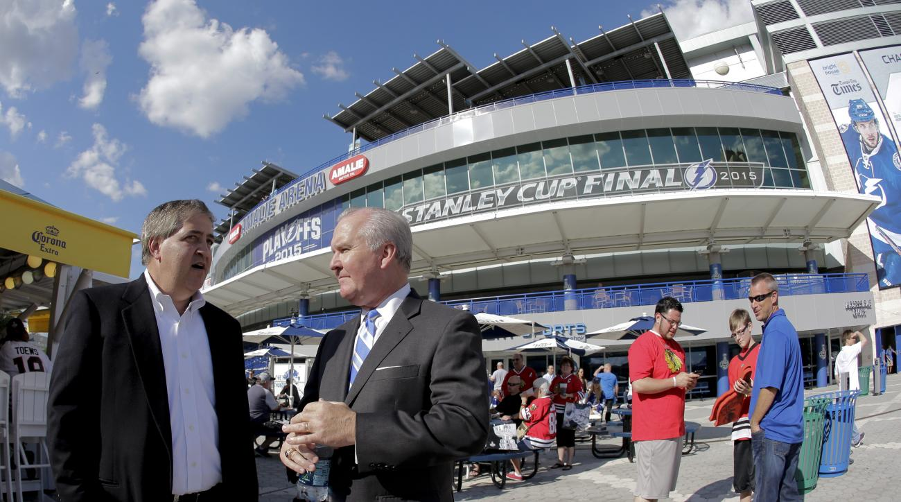 In this photo taken, Wednesday, June 3, 2015, Tampa Bay Lightning owner Jeff Vinik, left, chats with Tampa, Fla., Mayor Bob Buckhorn before Game 1 of the NHL hockey Stanley Cup Final in Tampa, Fla. While Sun Belt NHL teams from Phoenix to Miami struggle t