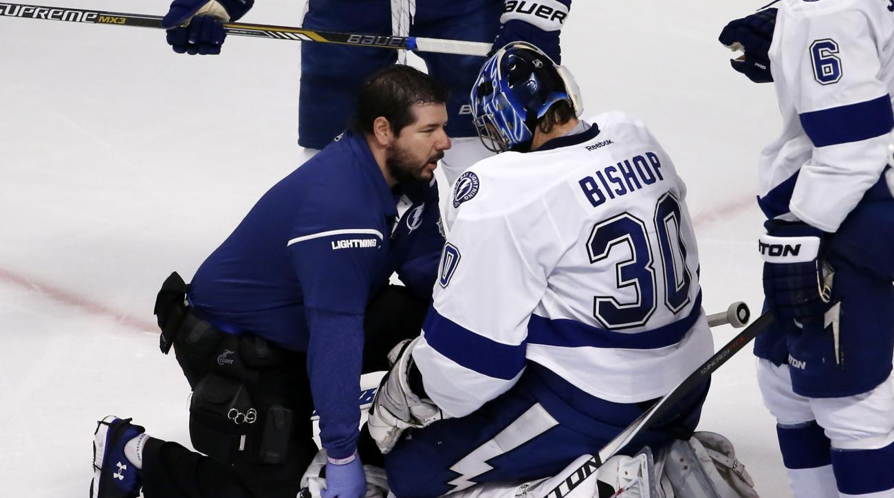 Tampa Bay Lightning goalie Ben Bishop is checked on by a trainer after being knocked down by Chicago Blackhawks' Brandon Saad during the second period in Game 3 of the NHL hockey Stanley Cup Final on Monday, June 8, 2015, in Chicago. (AP Photo/Charles Rex
