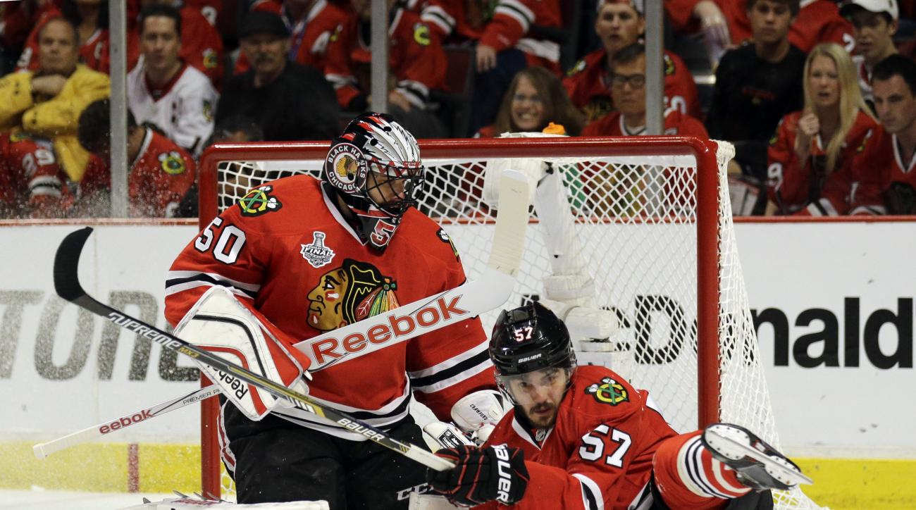 Chicago Blackhawks' Trevor van Riemsdyk, right, slides past goalie Corey Crawford while chasing after a loose puck during the third period in Game 3 of the NHL hockey Stanley Cup Final against the Tampa Bay Lightning on Monday, June 8, 2015, in Chicago. (