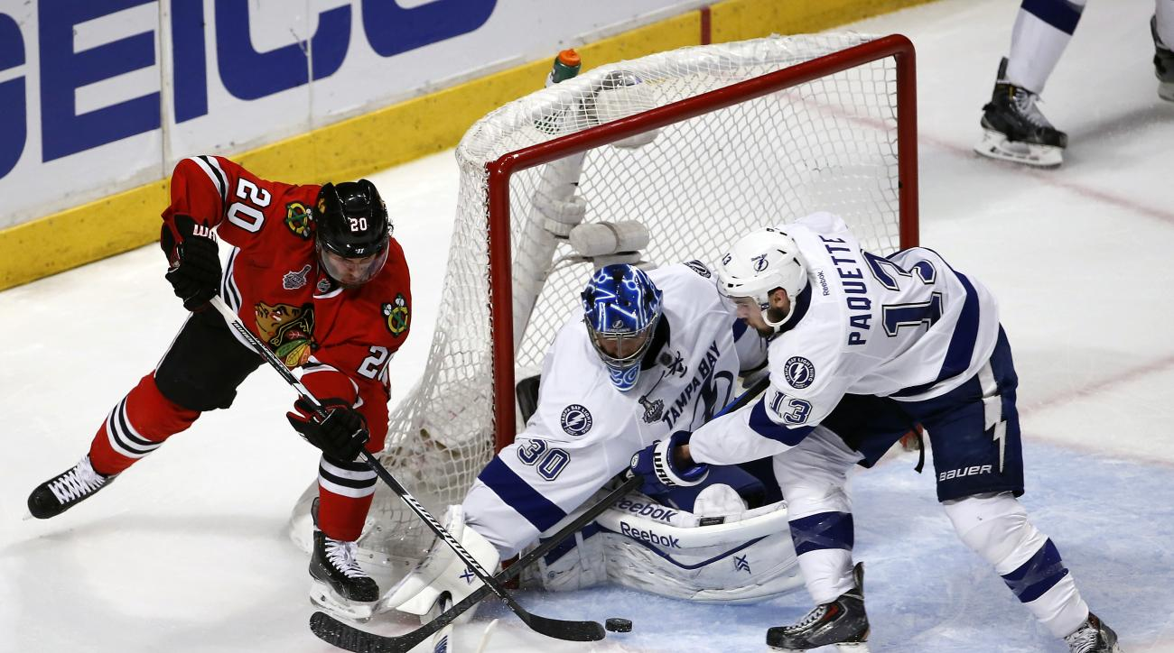 Chicago Blackhawks' Brandon Saad, left, reaches for a puck as Tampa Bay Lightning goalie Ben Bishop and Cedric Paquette, right, defend during the third period in Game 3 of the NHL hockey Stanley Cup Final on Monday, June 8, 2015, in Chicago. (AP Photo/Cha
