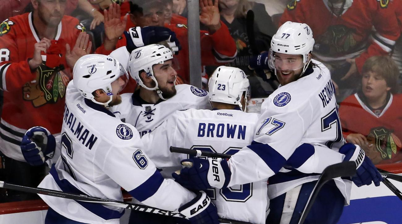 Tampa Bay Lightning's Cedric Paquette, second from left, is congratulated teammates Anton Stralman, left, J.T. Brown, and Victor Hedman, right, after scoring during the third period in Game 3 of the NHL hockey Stanley Cup Final against the Chicago Blackha