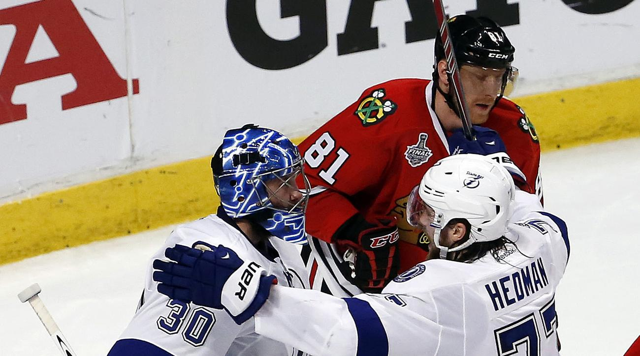 Tampa Bay Lightning goalie Ben Bishop (30) and Victor Hedman (77) celebrate as Chicago Blackhawks' Marian Hossa (81) skates past following the Lightning's 3-2 victory in Game 3 of the NHL hockey Stanley Cup Final on Monday, June 8, 2015, in Chicago. (AP P
