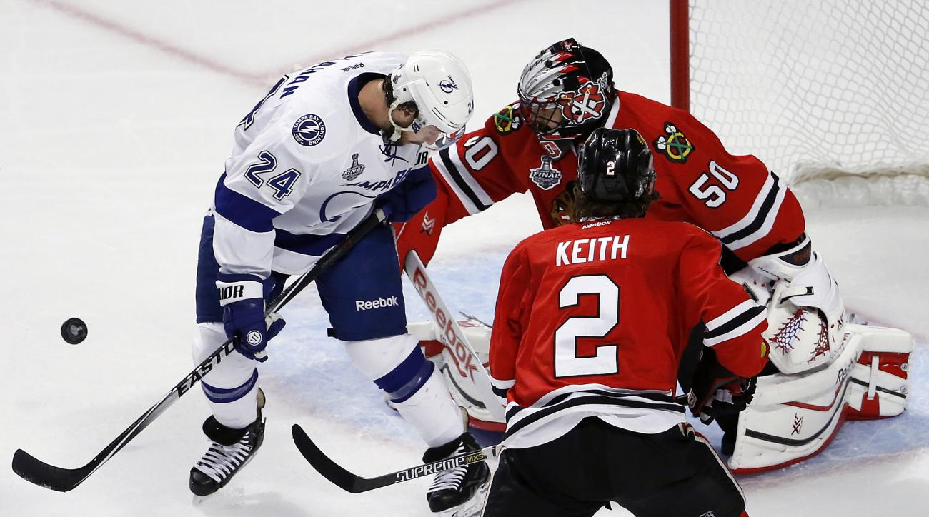Chicago Blackhawks goalie Corey Crawford (50) keeps his eye on the puck along side teammate Duncan Keith (2) and Tampa Bay Lightning's Ryan Callahan (24) during the first period in Game 4 of the NHL hockey Stanley Cup Final Wednesday, June 10, 2015, in Ch