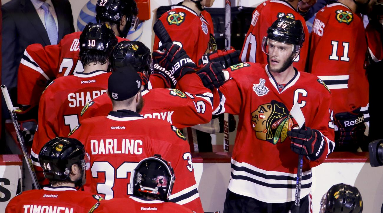 Chicago Blackhawks' Jonathan Toews, top right, celebrates with teammates after the Blackhawks' 2-1 victory over the Tampa Bay Lightning in Game 4 of the NHL hockey Stanley Cup Final Wednesday, June 10, 2015, in Chicago. The series is tied 2-2. (AP Photo/C