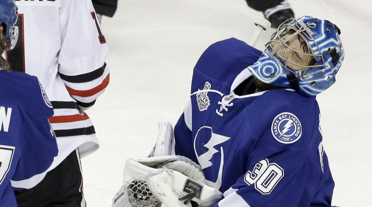 Tampa Bay Lightning goalie Ben Bishop (30) takes a hit from Chicago Blackhawks center Andrew Desjardins during the first period of Game 5 of the NHL hockey Stanley Cup Final, Saturday, June 13, 2015, in Tampa, Fla. (AP Photo/John Raoux)