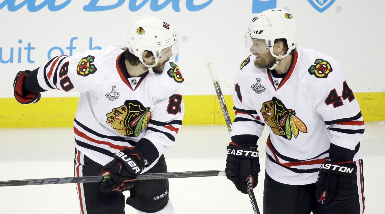 CORRECTS PLAYER AT RIGHT TO KIMMO TIMONEN, INSTEAD OF KRIS VERSTEEG - Chicago Blackhawks center Antoine Vermette (80) and defenseman Kimmo Timonen (44) react after Vermette scored a goal against the Tampa Bay Lightning of Game 5 of the NHL hockey Stanley