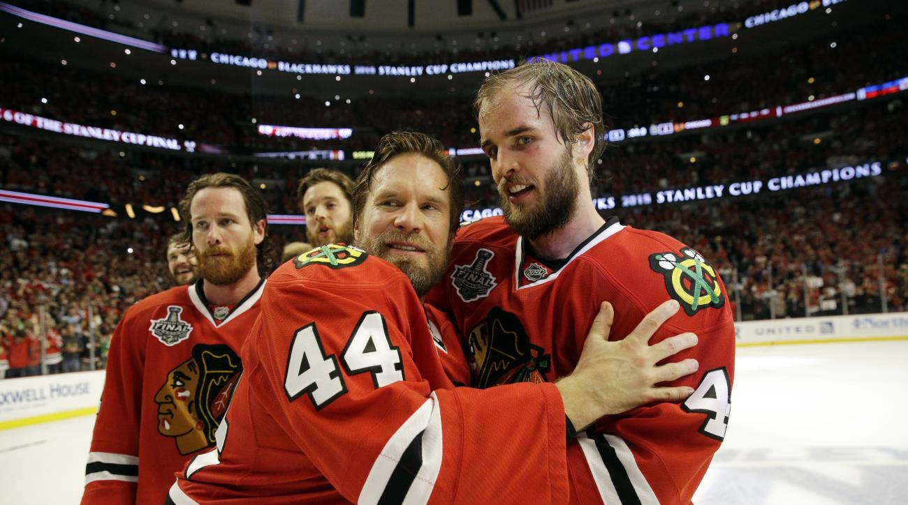 Chicago Blackhawks' Kimmo Timonen (44), of Finland, and Niklas Hjalmarsson (4), of Sweden, celebrate after defeating the Tampa Bay Lightning in Game 6 of the NHL hockey Stanley Cup Final series on Monday, June 15, 2015, in Chicago. The Blackhawks defeated