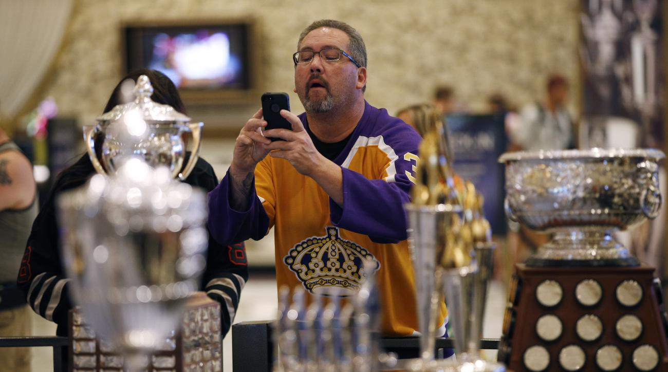 A fan takes pictures of NHL award trophies on display at the MGM Grand on Tuesday, June 23, 2015, in Las Vegas. The growing possibility of NHL expansion to Las Vegas is a popular topic among players and executives this week with the league in town for its
