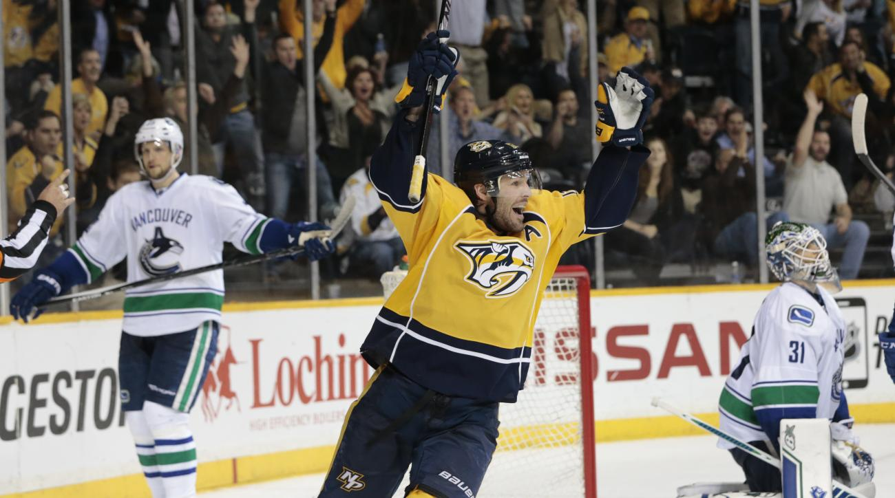 Nashville Predators forward Mike Fisher, center, celebrates after scoring a goal against  Vancouver Canucks goalie Eddie Lack (31), of Sweden, in the third period of an NHL hockey game Tuesday, March 31, 2015, in Nashville, Tenn. (AP Photo/Mark Humphrey)