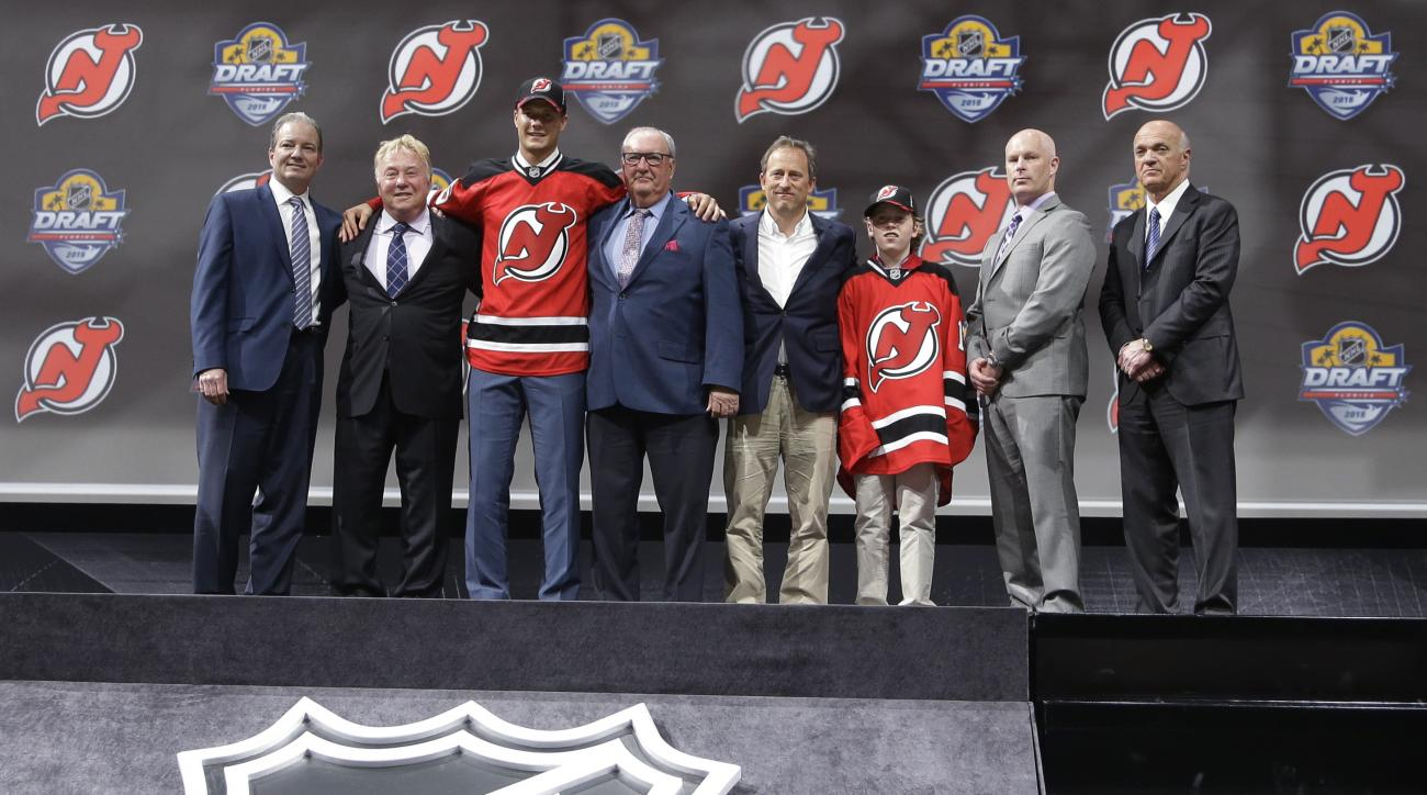 Pavel Zacha, third from left, of the Czech Republic, poses with executives with the New Jersey Devils after being picked sixth overall during the first round of the NHL hockey draft, Friday, June 26, 2015 in Sunrise, Fla. (AP Photo/Alan Diaz)