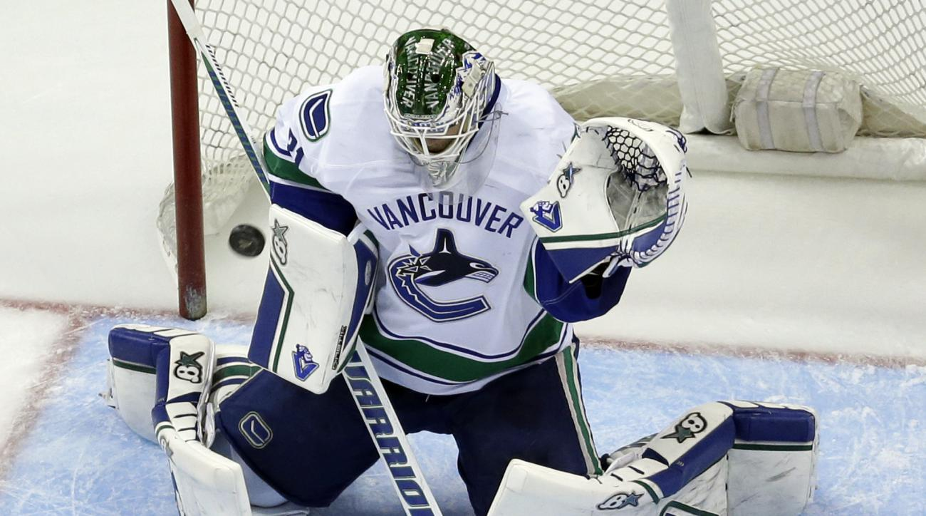 Vancouver Canucks goalie Eddie Lack, of Sweden, deflects a shot during the third period of an NHL hockey game against the St. Louis Blues Monday, March 30, 2015, in St. Louis. The Canucks won 4-1. (AP Photo/Jeff Roberson)