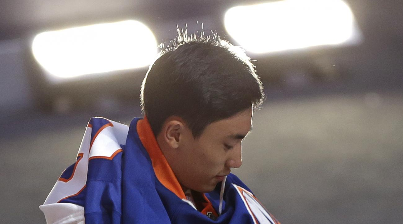 Andong Song, of China, puts on a sweater  after being chosen 172nd overall by the New York Islanders during the sixth round of the NHL hockey draft, Saturday, June 27, 2015, in Sunrise, Fla. (AP Photo/Alan Diaz)