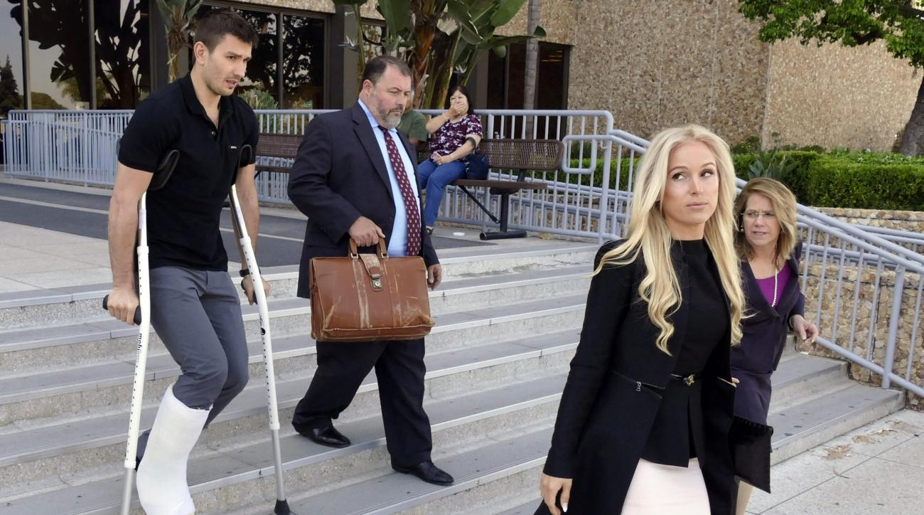 FILE - In this April 1, 2015, file photo, Los Angeles Kings player Slava Voynov, left, leaves court in Torrance, Calif., with his wife, Marta Varlamova, right front. Voynov pleaded no contest to a misdemeanor Thursday, July 2, 2015 in a domestic violence