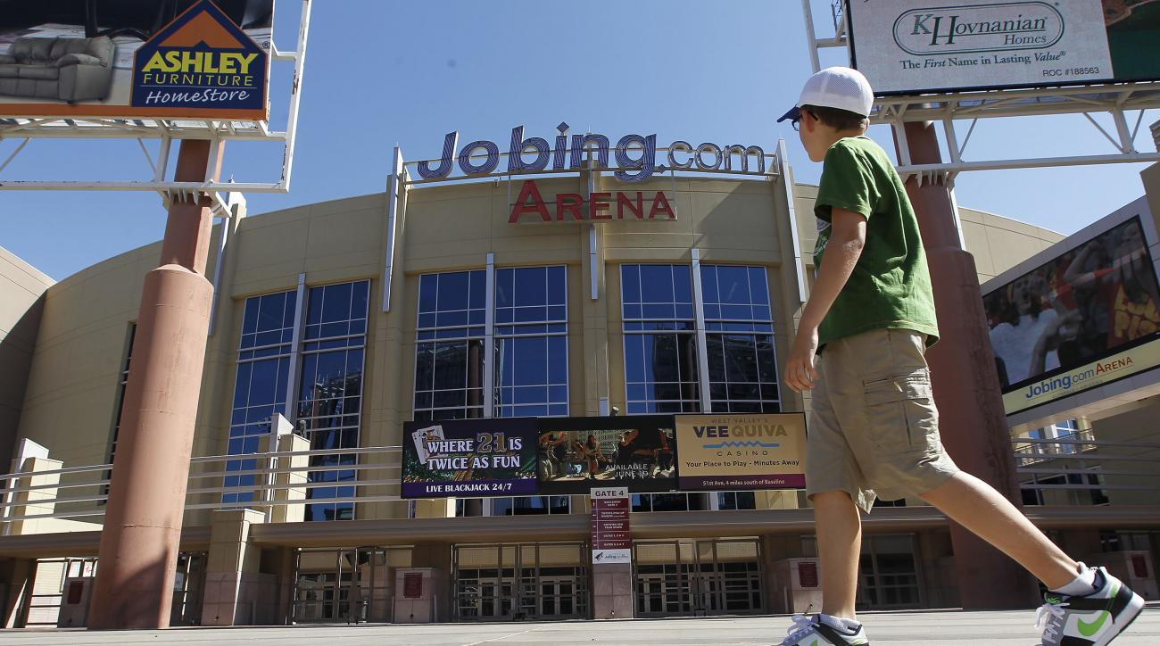 A lone pedestrian walks past Jobing.com Arena, Wednesday, June 13, 2012, in Glendale, Ariz., where the Phoenix Coyotes NHL hockey team plays home games.  The conservative watchdog group Goldwater Institute has filed a lawsuit seeking to invalidate the Gle