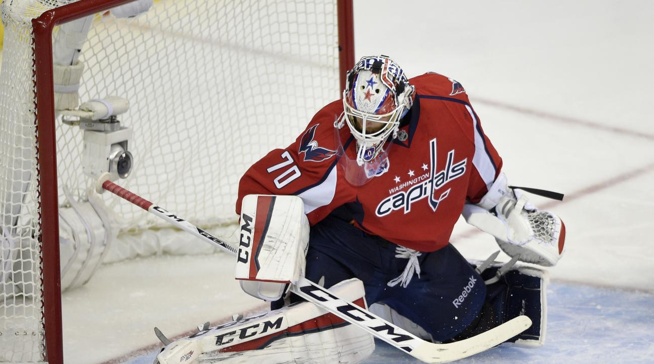Washington Capitals goalie Braden Holtby (70) stops the puck against the New York Rangers during the first period of Game 6 in the second round of the NHL Stanley Cup hockey playoffs, Sunday, May 10, 2015, in Washington. (AP Photo/Nick Wass)