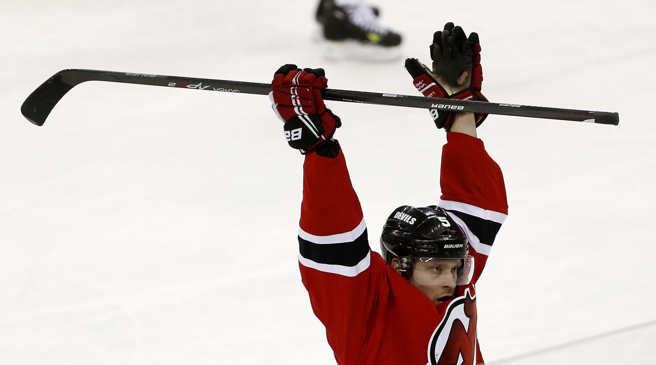 New Jersey Devils defenseman Adam Larsson, of Sweden, celebrates after scoring a goal against the Toronto Maple Leafs during the third period of an NHL hockey game, Wednesday, Jan. 28, 2015, in Newark, N.J. The Devils won 2-1 in a shootout. (AP Photo/Juli