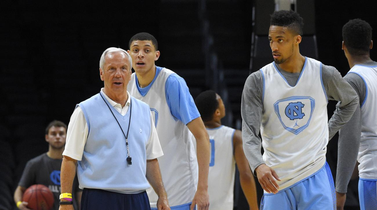 North Carolina head coach Roy Williams, left, watches as his players practice including forward Justin Jackson, center, and forward J.P. Tokoto, right, Wednesday, March 25, 2015, in Los Angeles, for a college basketball regional semifinal game in the NCAA