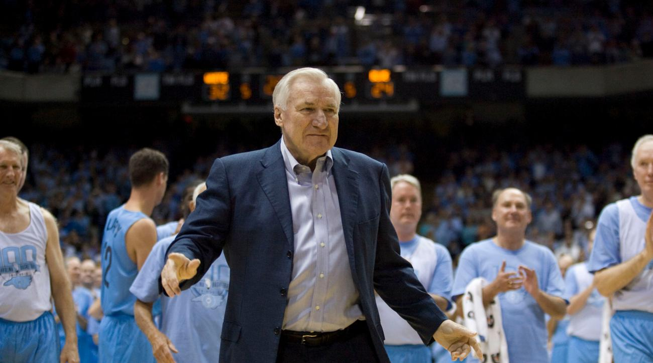 Surrounded by decades of former North Carolina  players, UNC coach Dean Smith acknowledges a standing ovation from the crowd after being honored  during the Celebration of a Century on Friday, Feb.  12, 2010, at the Smith Center in Chapel Hill, N.C..  (AP