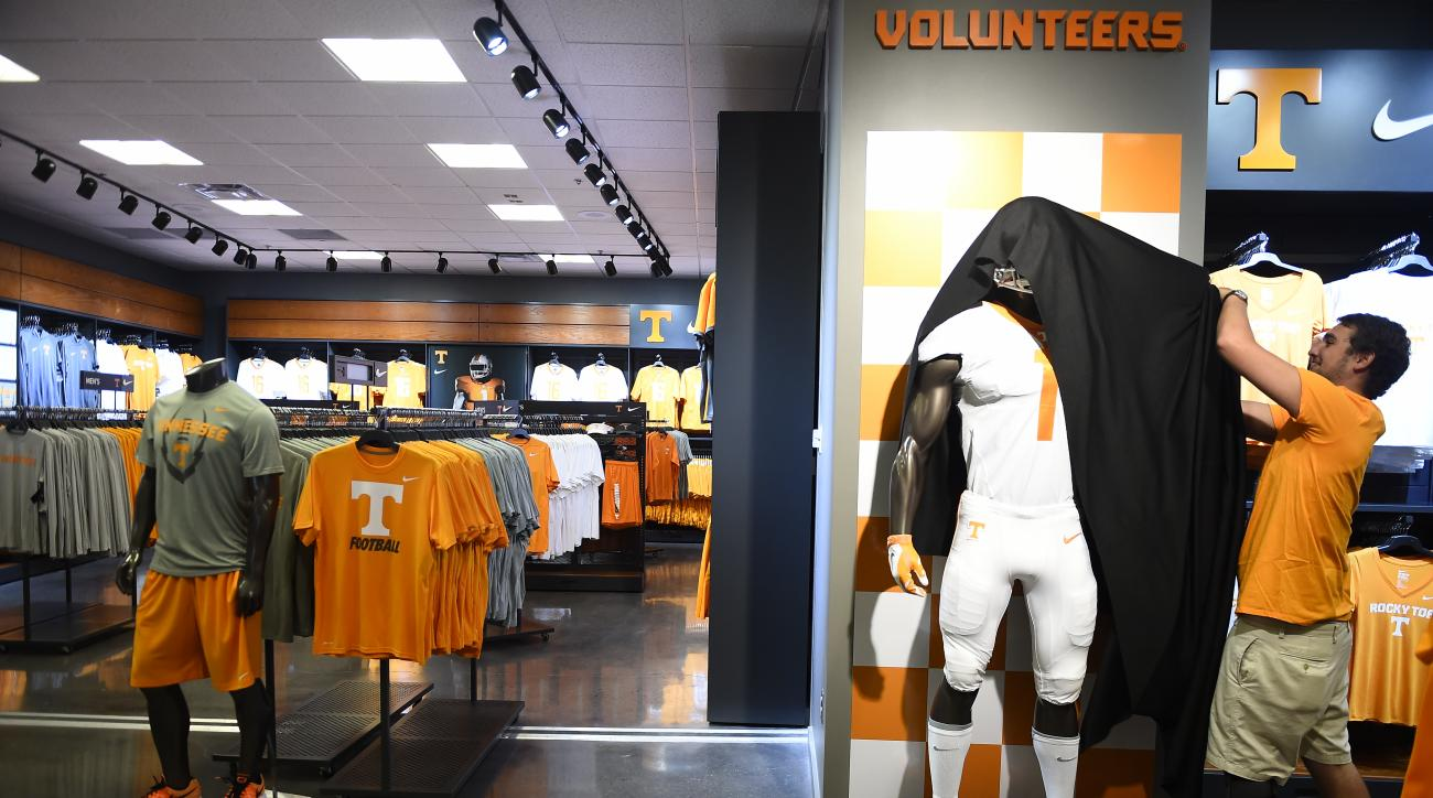 Vol Shop employee Thomas Shelton removes a cover from a mannequin with the new Nike football uniform inside Neyland Stadium, Wednesday, July 1, 2015. Nike took over as Tennessee's main apparel provider Wednesday as part of an eight-year contract worth abo
