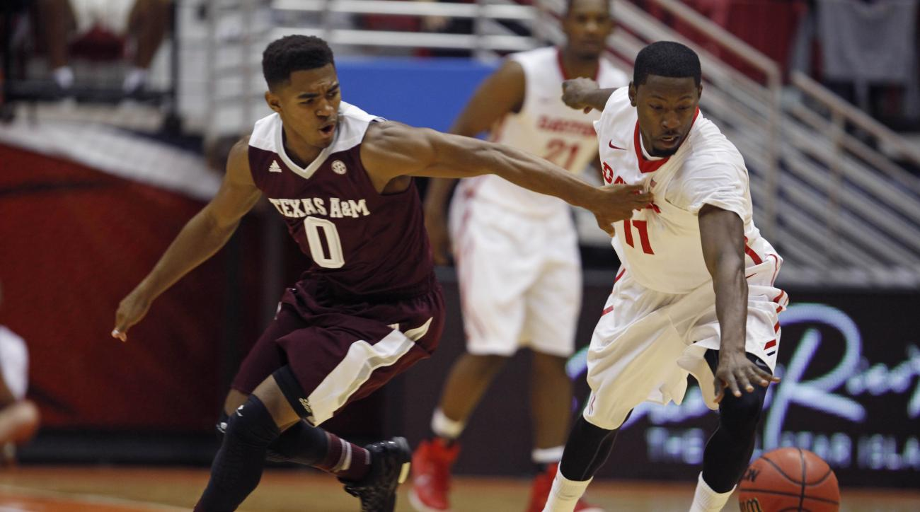 Dayton's Scoochie Smith, right, steals the ball from Texas A&M Avery Johnson during a NCAA college basketball game in San Juan, Puerto Rico, Thursday, Nov. 20, 2014. (AP Photo/Ricardo Arduengo)