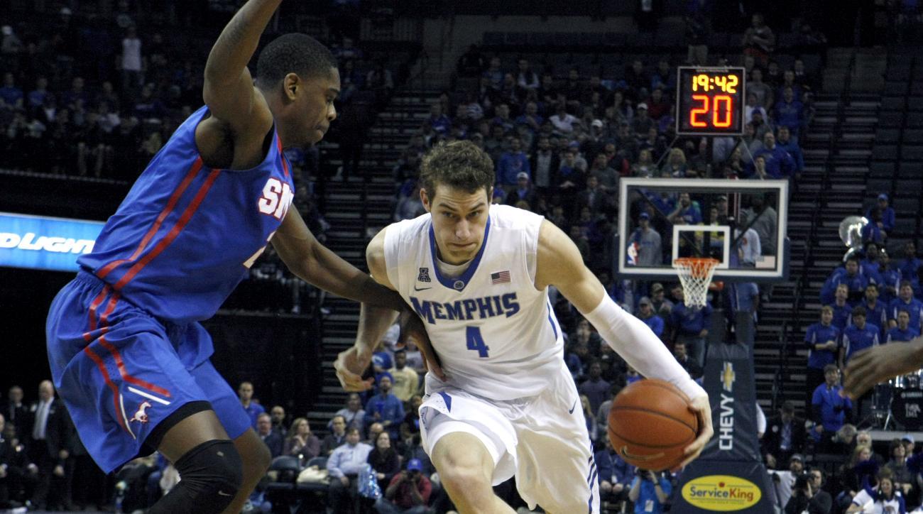 Memphis' Austin Nichols (4) powers past SMU's Yanick Moreira (2) in the first half of an NCAA college basketball game Thursday, Feb. 26, 2015, in Memphis, Tenn. (AP Photo/Karen Pulfer Focht)
