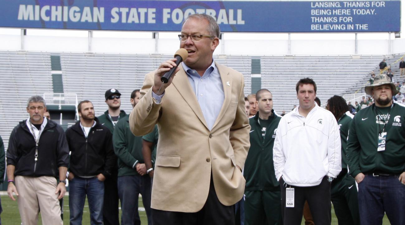 FILE - In this April 26, 2014, file photo, Michigan State athletic director Mark Hollis introduces members of the 2013 Big Ten Championship and 2014 Rose Bowl Championship team during halftime of an NCAA college spring football scrimmage in East Lansing,