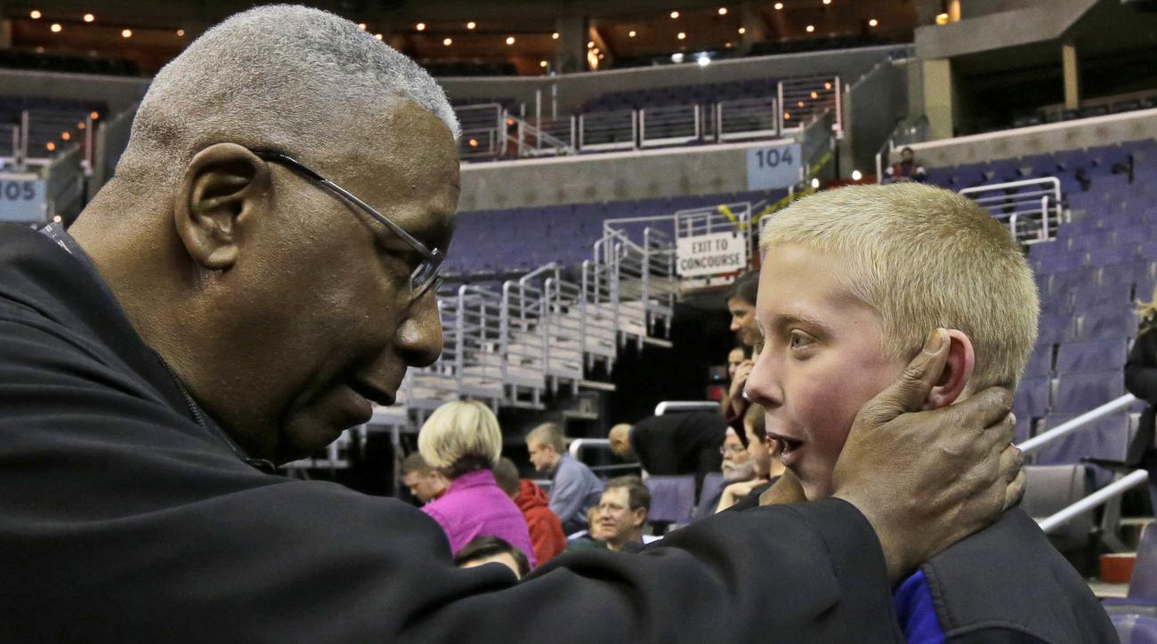 Former Georgetown coach John Thompson, Jr. greets Braden Porterfield, 10, from Alexandria, Va., during Miami's practice for a regional semifinal game in the NCAA college basketball tournament, Wednesday, March 27, 2013, in Washington. Miami will face Marq