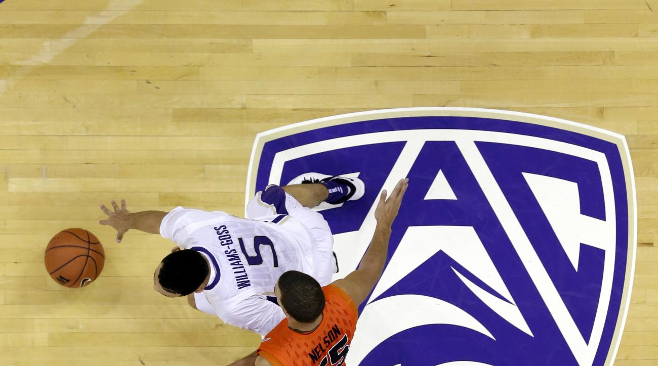 FILE - In this Jan. 25, 2014, file photo, Washington's Nigel Williams-Goss (5) dribbles past Oregon State's Roberto Nelson and across a Pac-12 logo in the first half of an NCAA college basketball game in Seattle. The Pac-12 has proposed changing NCAA rule