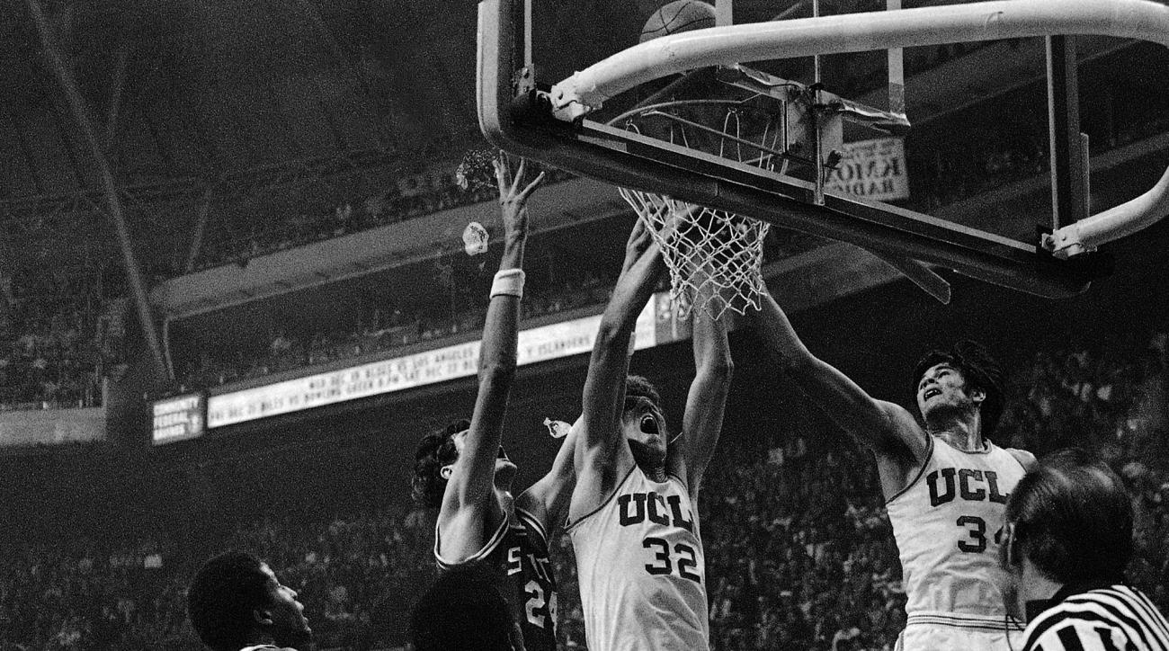 FILE - In this Dec. 15, 1973, file photo, UCLA's Bill Walton (32) and Dave Meyers, right, reach for a rebound following a shot by North Carolina State's Tommy Burleson (24) during an NCAA college basketball game in St. Louis. Meyers, the star forward who