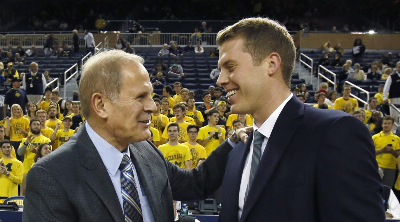 Michigan head coach John Beilein, left, greets his son, right, Le Moyne head coach Patrick Beilein, before an NCAA college basketball exhibition game Friday, Nov. 6, 2015, in Ann Arbor, Mich. (AP Photo/Duane Burleson)
