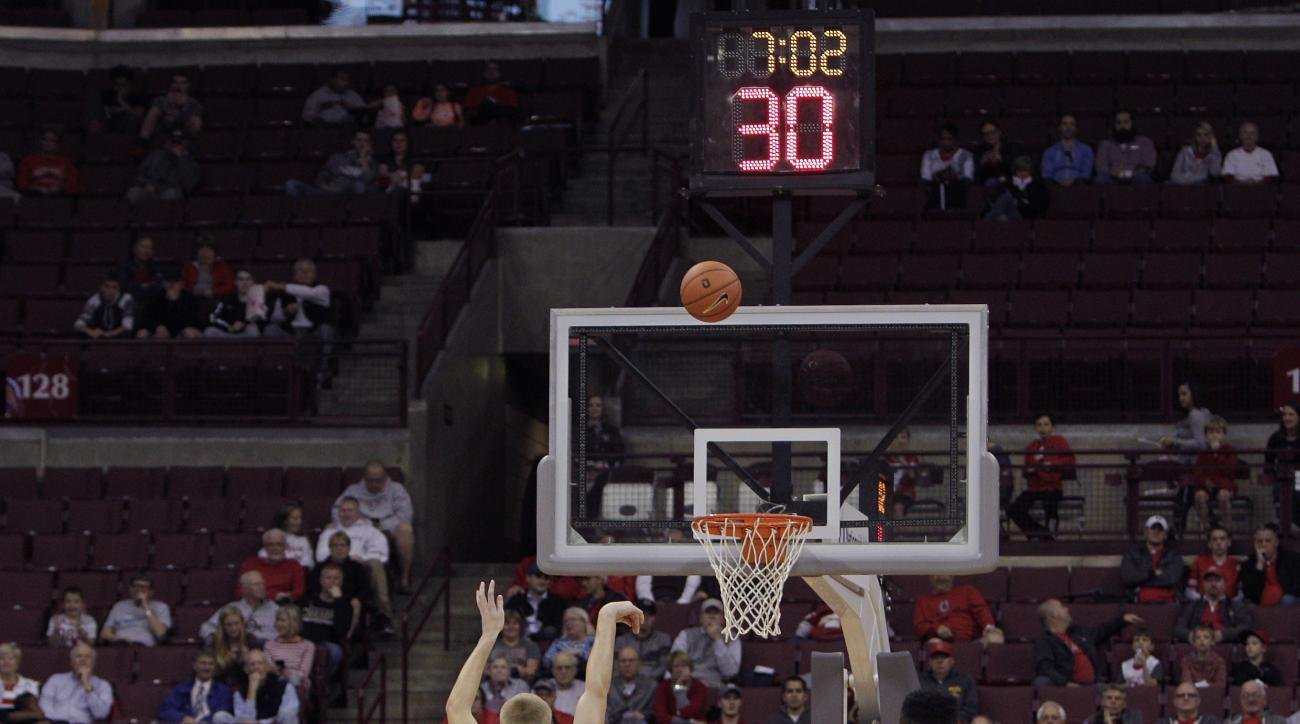 FILE - In this Nov. 8, 2015, file photo, the shot clock is at 30 seconds as Walsh's Conor Keck (4) shoots a free throw against Ohio State during the first half of an exhibition NCAA college basketball game, in Columbus, Ohio. The NCAA has shaved 5 seconds