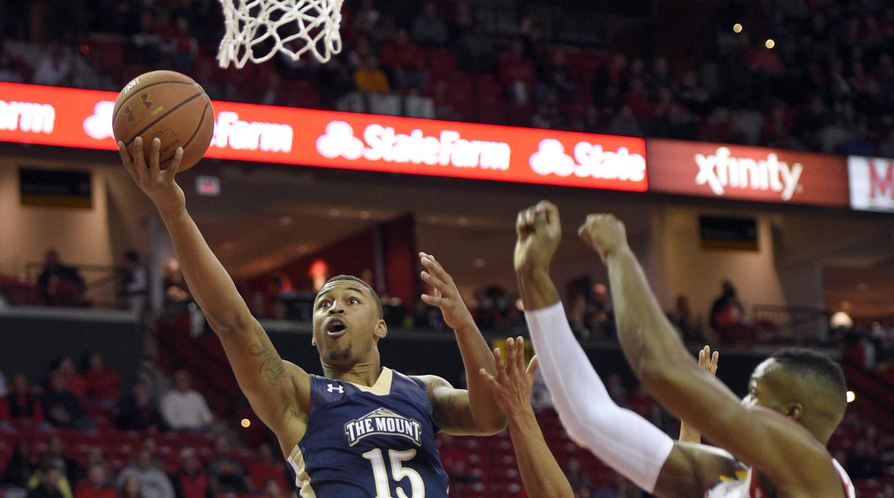 Mount St. Mary's forward Gregory Graves (15) goes to the basket against Maryland guard Melo Trimble (2) and Robert Carter (4) during the first half of an NCAA college basketball game, Friday, Nov. 13, 2015, in College Park, Md. (AP Photo/Nick Wass)