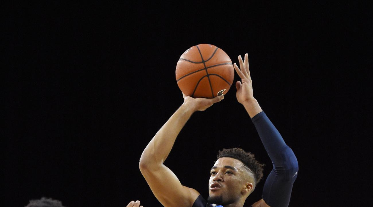 San Diego guard Olin Carter III, center, shoots as Southern California guard Malik Marquetti, left, and guard Jordan McLaughlin defend during the first half of an NCAA college basketball game, Friday, Nov. 13, 2015, in Los Angeles. (AP Photo/Mark J. Terri