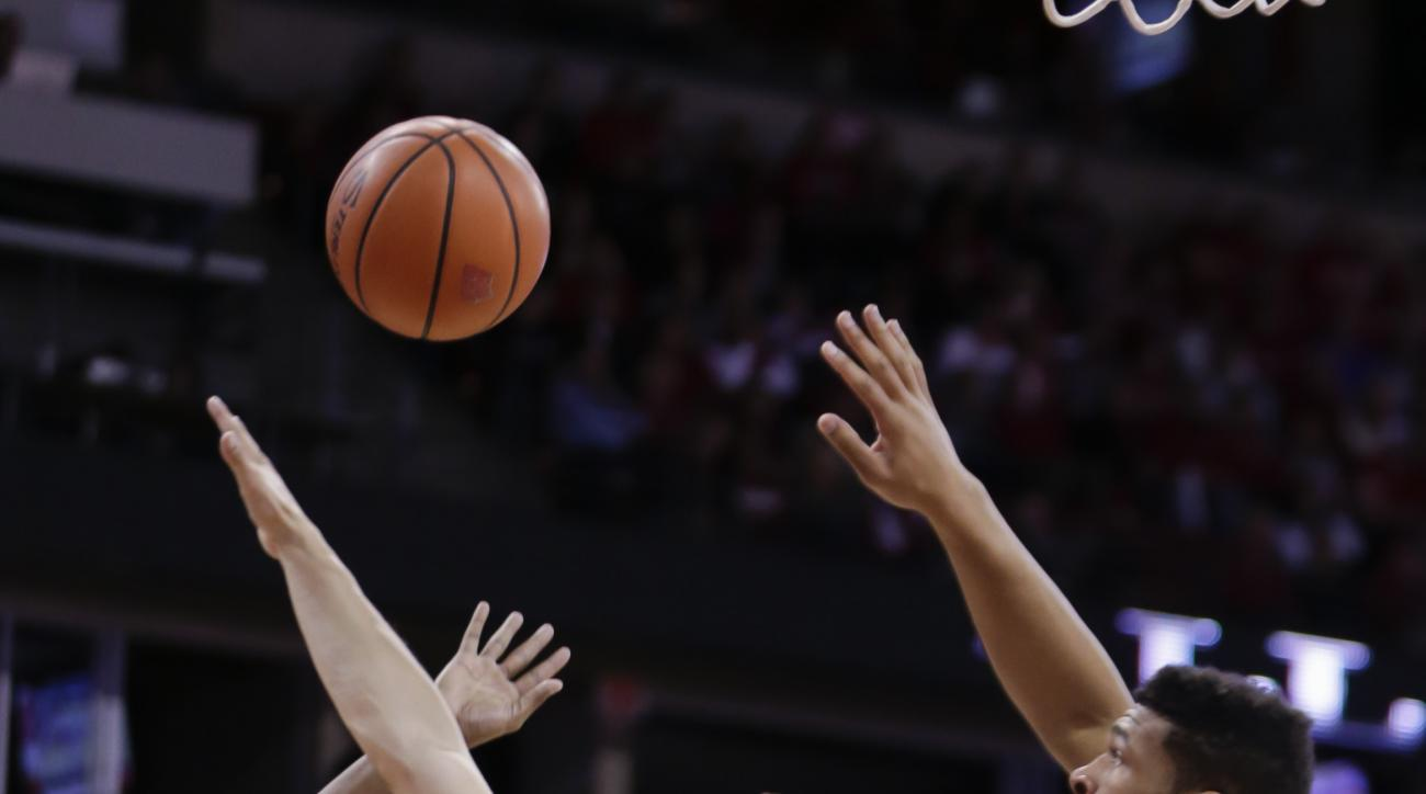 Wisconsin's Bronson Koenig (24) fouls Western Illinois' Jabari Sandifer (1) during the first half of an NCAA college basketball game Friday, Nov. 13, 2015, in Madison, Wis. At right is Wisconsin's Charlie Thomas. (AP Photo/Andy Manis)