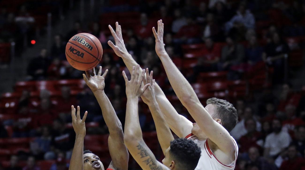 Southern Utah guard Travon Langston (3) shoots as Utah's Kyle Kuzma (35) and Jakob Poeltl, right, defend in first half during an NCAA college basketball game Friday, Nov. 13, 2015, in Salt Lake City. (AP Photo/Rick Bowmer)