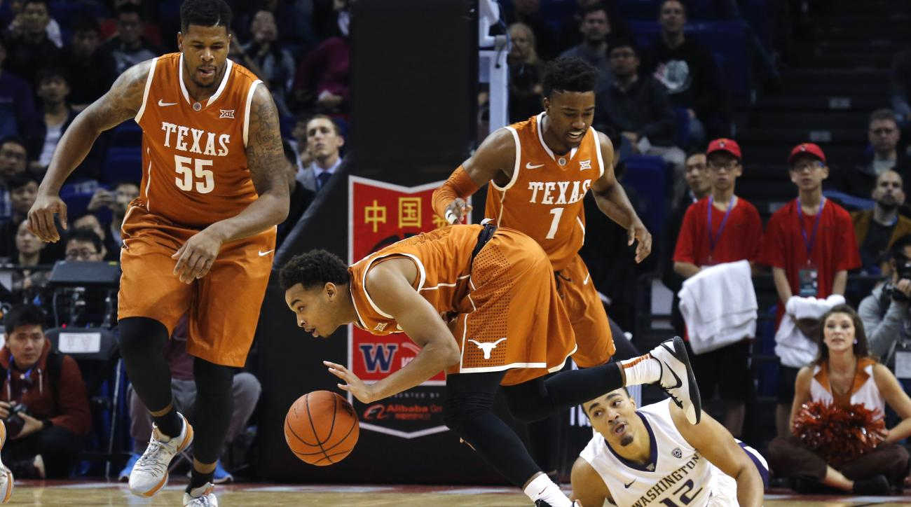 Andrew Andrews of the Washington Huskies in white watches as Eric Davis, Jr. of the Texas Longhorns dribbles the ball past during a college basketball match at the Mercedez Benz Arena in Shanghai, China, Saturday, Nov. 14, 2015. Chinese characters at the