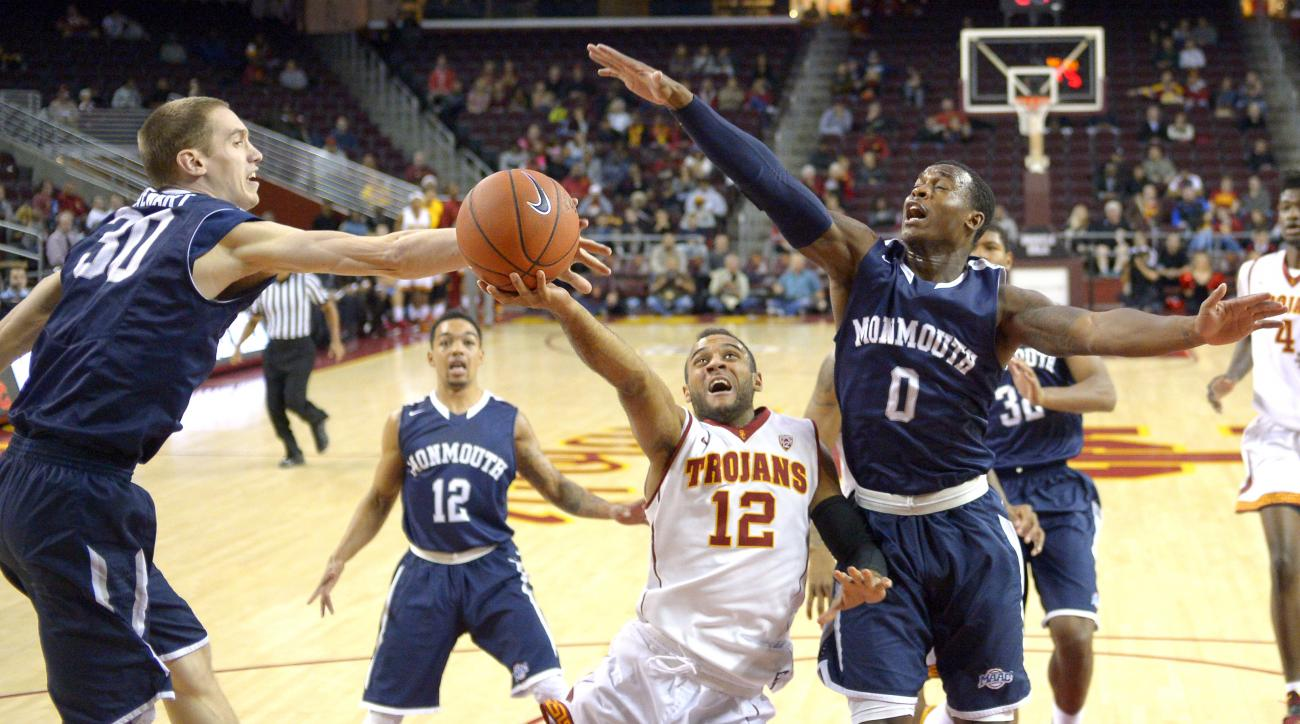 Southern California guard Julian Jacobs, second from right, puts up a shot as Monmouth guard Collin Stewart, left, and guard Josh James, right, defend while guard Justin Robinson watches during the first half of an NCAA college basketball game, Monday, No